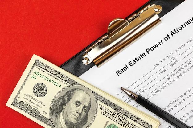 Formular zur immobilienvollmacht. schreibtisch und zwischenablage mit vereinbarung und geld. foto von oben