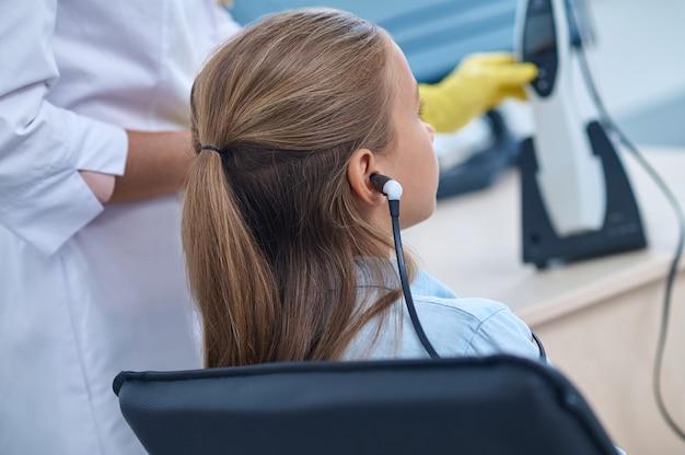 Forschen, hören. rückansicht eines langhaarigen grundschulmädchens, das spezielle kopfhörer und einen arzt in der hno-arzt trägt