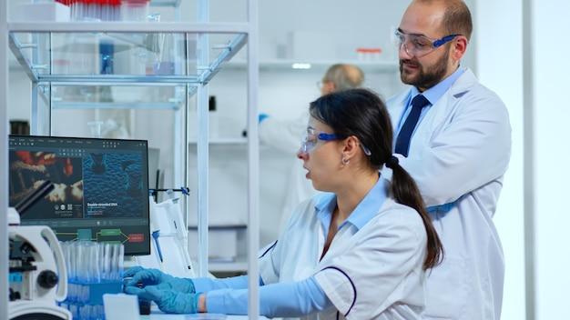 Forscher arbeiten am pc mit medizinischen geräten, die blut- und genetische materialproben mit einem speziellen programm in einem modern ausgestatteten labor analysieren. multiethnisches team untersucht virusentwicklung