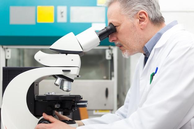 Forscher, der mikroskop in einem labor verwendet