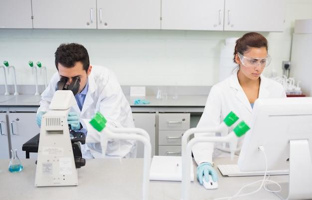 Forscher, die mikroskop und computer im labor verwenden