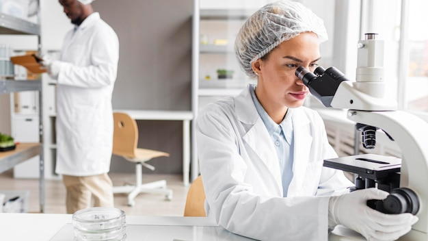 Forscher im biotechnologielabor mit tablette und mikroskop