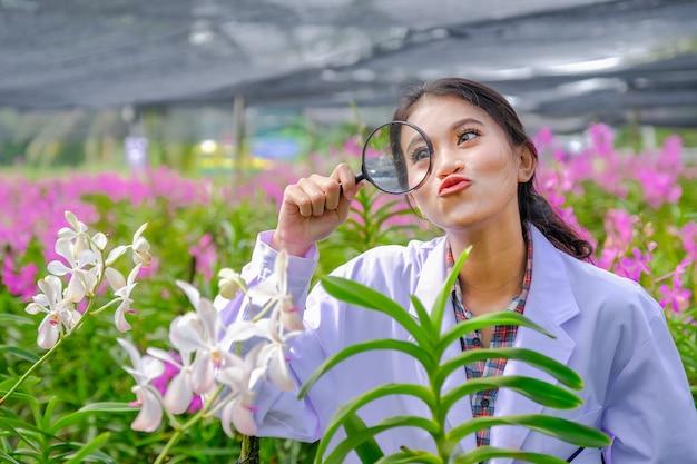 Forscher, junge frauen in weißen kleidern, die orchideen untersuchen