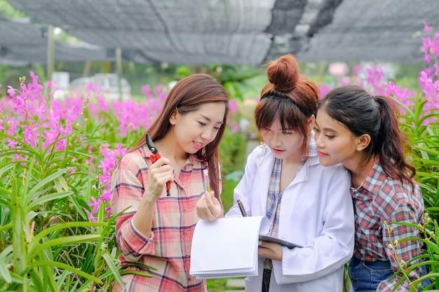 Forscher, junge frauen in weißen kleidern und besitzer von orchideengärten arbeiten mit orchideen zusammen