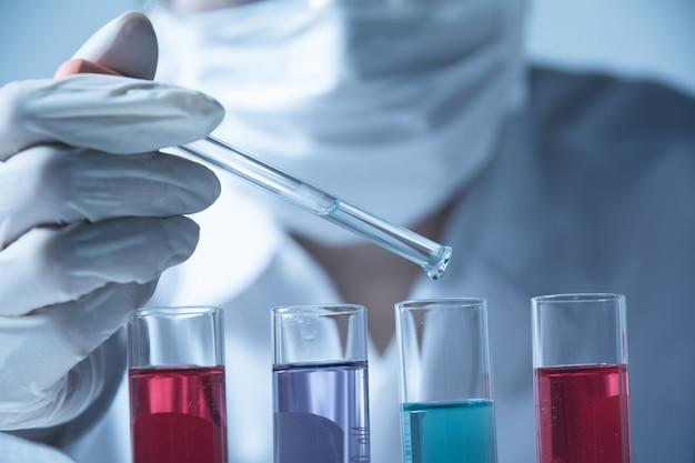 Forscher mit chemischen laborreagenzgläsern mit flüssigkeit
