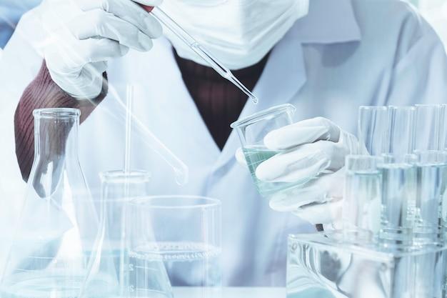 Forscher mit chemischen reagenzgläsern des glaslabors mit flüssigkeit für analytisches