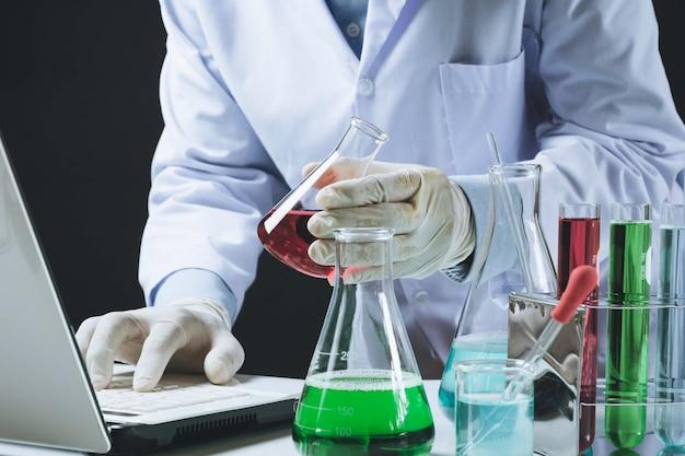 Forscher mit chemischen reagenzgläsern des glaslabors mit flüssigkeit