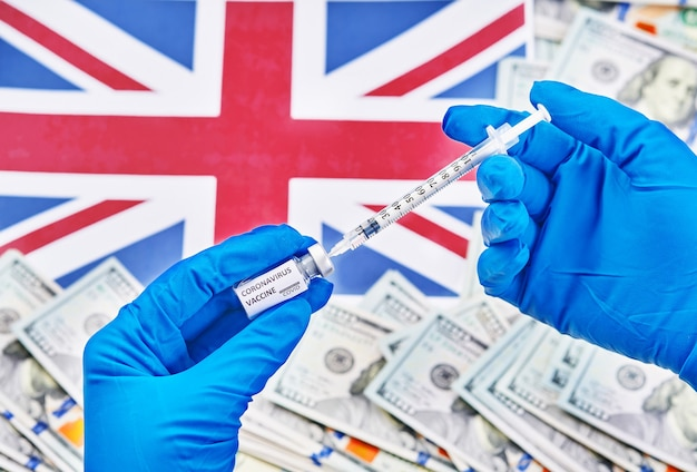 Forscherhand in den blauen handschuhen, die coronavirus, covid-19-impfstoff gegen hintergrund der flagge von england und geldkrankheit halten, die für impfschuß der klinischen studien des menschen, medizinkonzept vorbereiten.