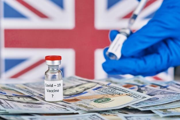 Forscherhand in den blauen handschuhen, die den covid-19-impfstoff vor dem hintergrund der flagge von england und der geldkrankheit halten, die für impfimpfung der klinischen studien des menschen vorbereiten, medizinkonzept.
