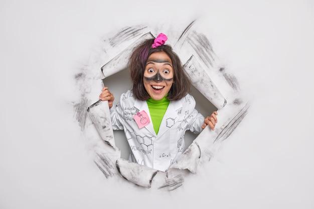 Forscherin, die schmutzig ist, nachdem sie ein chemisches experiment in einem medizinischen kittel durchgeführt hat, bricht durch papier