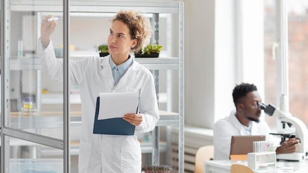 Forscherin mit zwischenablage im biotechnologielabor und kollegin