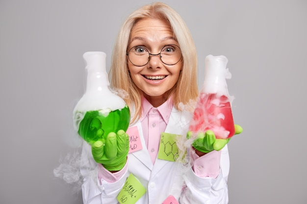 Forscherin untersucht chemische experimente zeigt flüssigkeit mit dampf überrascht mit ergebnissen trägt laborkittel gummischutzhandschuhe posiert auf grau