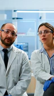 Forscherteam, das virtuelles display mit touchscreen, virtuelle realität mit medizinischer innovation im labor betrachtet, gestikuliert. wissenschaftler, die mit ausrüstung, zukunft, gesundheitswesen, vision, si . arbeiten