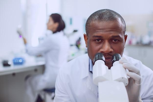 Forschung betreiben. erfahrene erfahrene forscher, die während der arbeit im labor an seinem mikroskop arbeiten