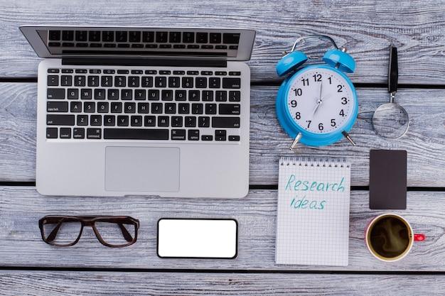 Forschungsideen konzept. laptop-pc mit smarthone und glaslupe. büroarbeitsgegenstände flach.
