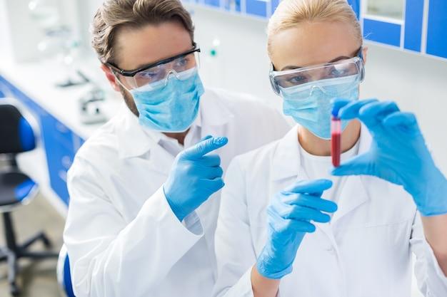 Forschungsmaterial. nette positive intelligente biologen, die zusammenstehen und auf die blutprobe zeigen, während sie sie studieren