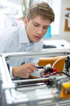 Fortgeschrittene technologie. angenehmer junger mann, der ein gedrucktes modell mit einem digitalen messschieber während der arbeit im büro misst