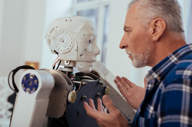 Fortschrittliche technologie. ernsthafter kluger ingenieur, der den roboter betrachtet, während er vor ihm steht