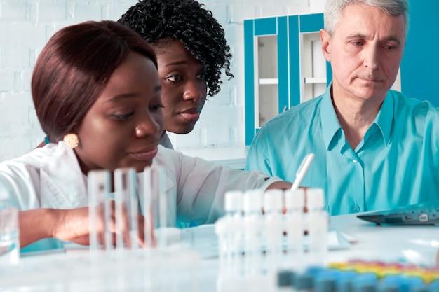 Fortschrittsbericht im prüflabor. weibliche afrikanische medizinstudenten, absolventen, die dem kaukasischen mann, dem leiter der senorgruppe, daten zeigen. durchführen von blut- und nukleinsäuretests auf coronavirus, das covid-19 verursacht.