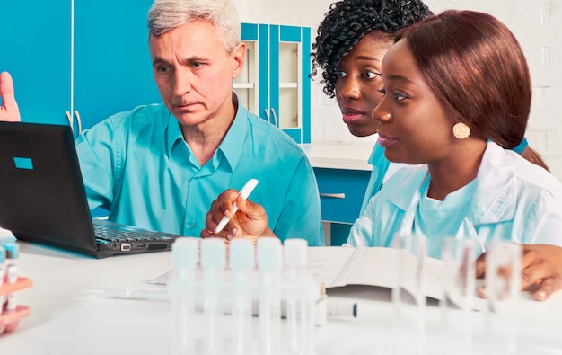 Fortschrittsbericht im prüflabor. weibliche afrikanische medizinstudenten, absolventen, die dem kaukasischen mann, dem wissenschaftlichen berater des senors, daten zeigen. führen sie in fällen von covid-19-lungenentzündung einen blut- und pcr-test auf das coronavirus durch.