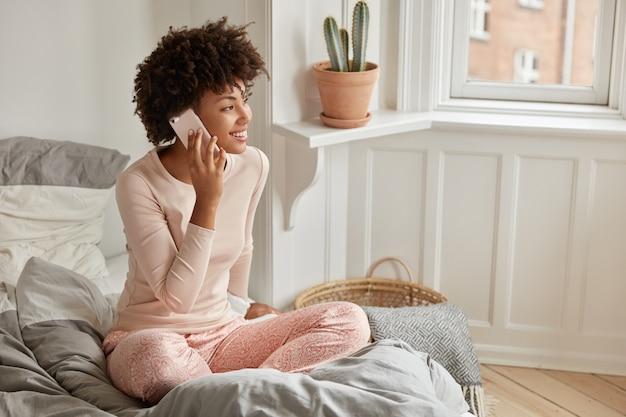 Foto der afroamerikanischen dame macht termin über handy, gekleidet in freizeitkleidung, sitzt in lotushaltung auf dem bett, trägt freizeitkleidung, unterhält sich mit freunden, hat freien tag, posiert im schlafzimmer