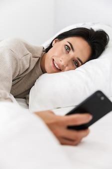 Foto der alleinstehenden frau 30s mit smartphone, während im bett mit weißer wäsche zu hause liegen