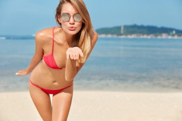 Foto der angenehm aussehenden schönen jungen frau hat erholung während der sommerferien, trägt rote badebekleidung, bläst luftkuss, posiert gegen meerblick mit kopierraum für ihre werbung oder text