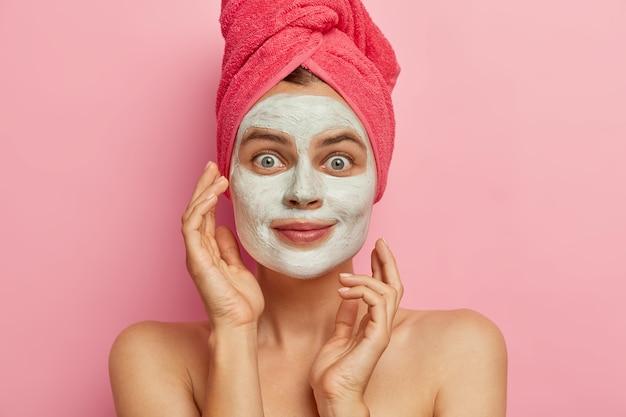 Foto der attaraktiven jungen frau wendet nahrhafte gesichtsmaske für gesichtspflege an, will saubere frische haut haben, trägt rosa handtuch auf kopf