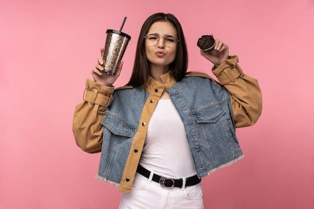 Foto der attraktiven dame hält tee-kaffee-muffins glücklich zeigt liebe, trägt lässige jeansjacke weißes unterhemd isoliert rosa hintergrund.