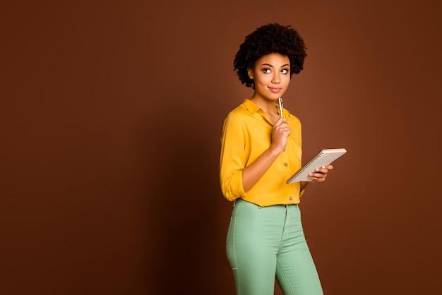 Foto der attraktiven dunklen haut lockige dame autor halten tagebuch blick leeren raum warten kreative gedanken inspiration tragen gelbes hemd grüne hose isoliert braune farbe