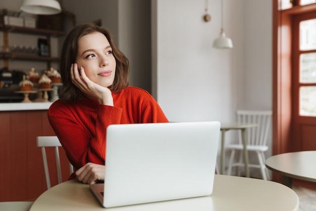 Foto der attraktiven frau 20s im lässigen pullover, der beiseite schaut, während am tisch im café mit laptop sitzt
