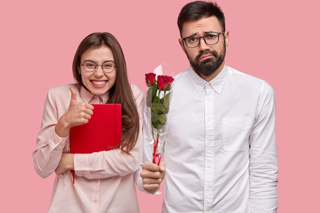 Foto der attraktiven frau zeigt zustimmungsgeste, hält daumen hoch, trägt roten notizblock, verwirrter unrasierter mann hält strauß rosen