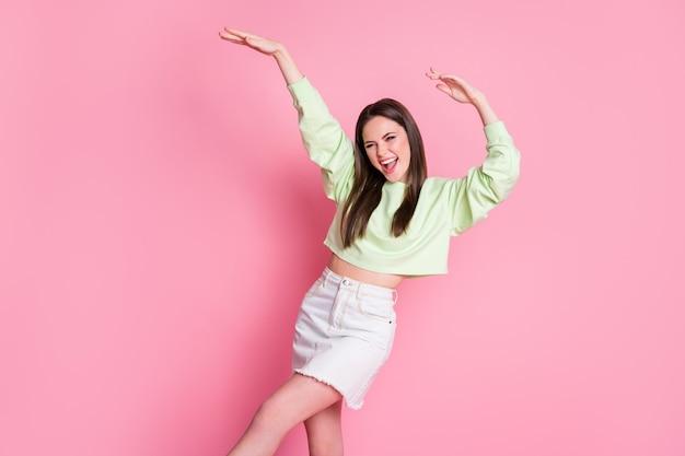 Foto der attraktiven funky jungen tausendjährigen dame hebt die arme tanzende studenten party schlanke figur tragen lässigen grünen pullover mit nacktem bauch jeansrock isoliert rosa hintergrund