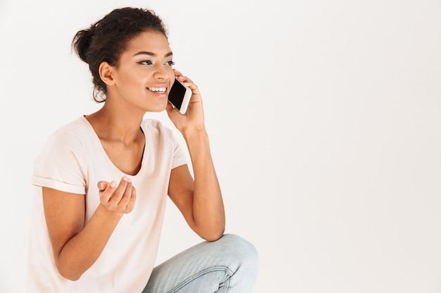 Foto der attraktiven gemischten rassenfrau im lässigen lächeln und sprechen auf handy, lokalisiert über weißer wand
