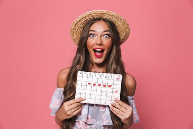 Foto der attraktiven glamourfrau, die strohhut hält menses kalender