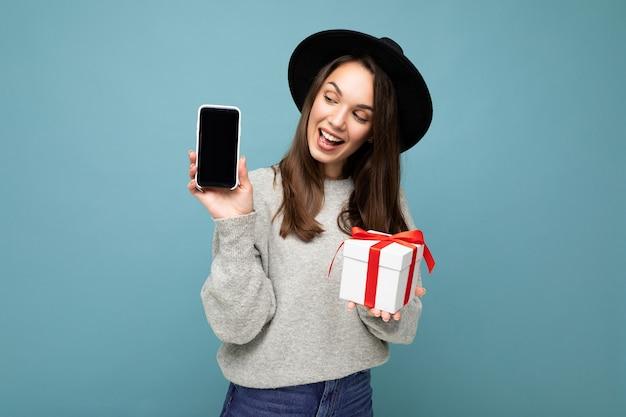 Foto der attraktiven glücklichen fröhlichen jungen brünetten weiblichen person lokalisiert über blauer hintergrundwand