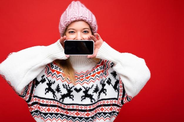 Foto der attraktiven glücklichen jungen blonden frau mit warmer strickmütze und warmem winterpullover