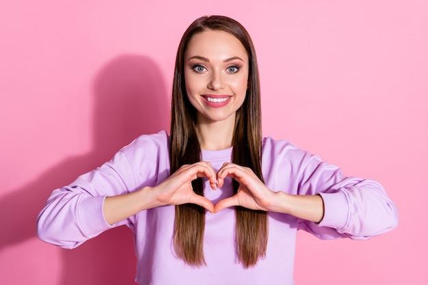Foto der attraktiven hübschen dame gute laune hände, die herzsymbol zeigen, drücken herzgefühle aus romantische datumseinladung tragen lässigen lila pullover isoliert rosa pastellfarbenen hintergrund