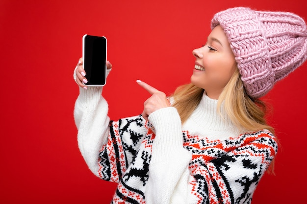 Foto der attraktiven lächelnden jungen blonden frau, die warmen strickmütze und warmen winterpullover trägt