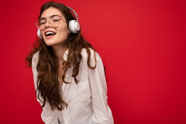 Foto der attraktiven positiv lächelnden jungen brunetfrau, die weißes hemd und optische brille trägt