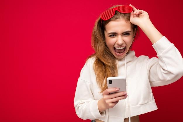 Foto der attraktiven verrückten überraschten überraschten jungen frau, die lässige stilvolle kleidung trägt, die isoliert steht