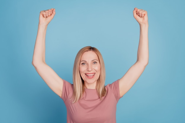 Foto der aufgeregten frau glückliches positives lächeln freuen sich über sieg glückliche erfolgsfäuste hände einzeln auf blauem hintergrund