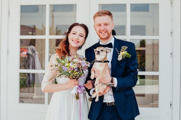 Foto der braut und des bräutigams an ihrem hochzeitstag mit ihrem kleinen hund