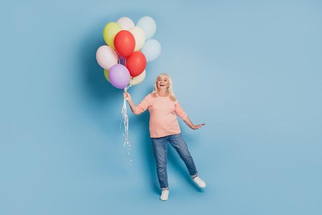 Foto der charmanten alten frau hält viele luftballons in rosa pullover auf blauem hintergrund
