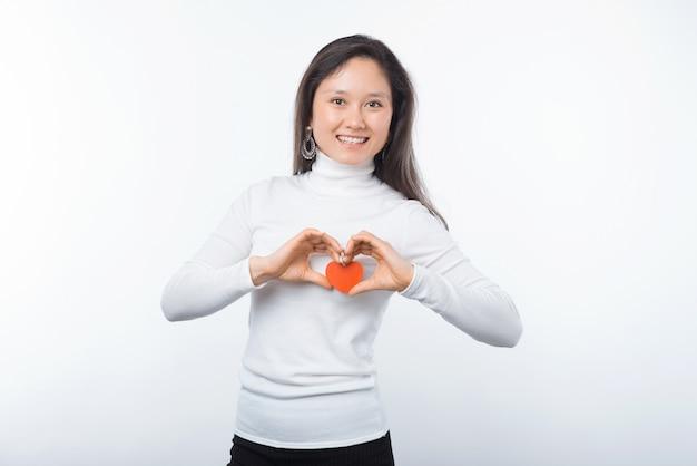 Foto der charmanten jungen asiatischen frau, die rotes papierherz über weißem hintergrund lächelt und hält