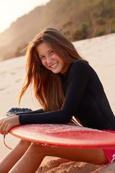 Foto der dunkelhaarigen positiven jungen surfboarderin im badeanzug, lehnt sich an das surfbrett, posiert in der reihe, atmet frische meeresluft