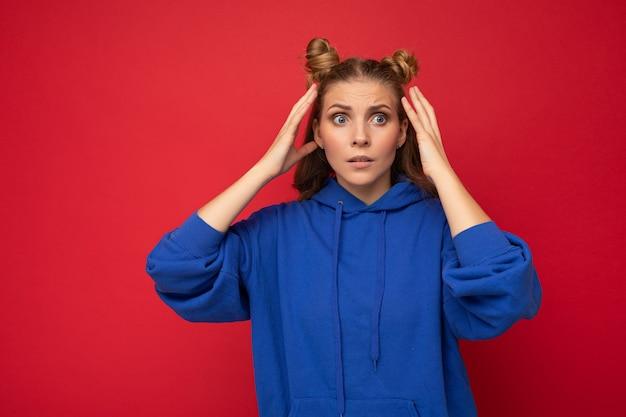 Foto der emotional überraschten verblüfften jungen schönen blonden frau mit zwei hörnern mit aufrichtigen gefühlen, die den hellblauen kapuzenpulli des hipsters tragen, der über rotem hintergrund mit freiem raum isoliert wird.