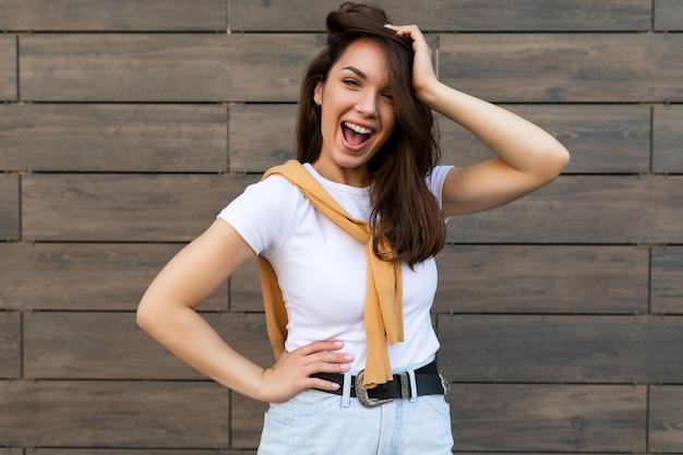 Foto der emotionalen positiven glücklichen freudigen hübschen jungen brünettenfrau im trendigen outfit schön