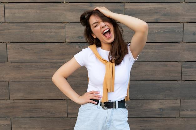 Foto der emotionalen positiven glücklichen fröhlichen hübschen jungen brunettefrau im modischen outfit schön