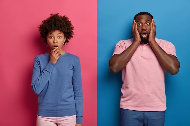 Foto der emotionalen schwarzen frau und des mannes keuchen vor staunen und schock, hören schreckliche nachrichten, stellen fest, dass ein schrecklicher unfall mit einem freund passiert ist